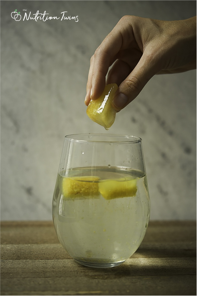 Ginger turmeric ice cube with hand over glass of water